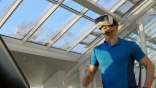 Middle-aged man running on treadmill at the gym, wearing VR glasses and enjoying virtual worlds