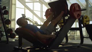 Middle-aged man working out with leg press machine at the gym during sunset