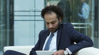 Middle eastern businessman sitting on couch in lobby of modern office center and using digital tablet; businesswoman walking in background