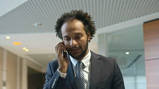 Middle eastern businessman walking through office center and speaking on cell phone