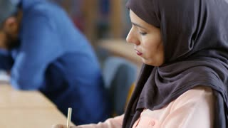 Migrant female student in hijab writing answers for test while passing exam in language school