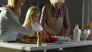 Mother, little daughter and grandmother cooking together apple pie in the kitchen for family dinner