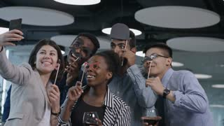 Multi-ethnic team of business men and women holding paper mustache and eyeglasses on sticks, smiling and making funny faces at camera of smartphone while taking selfie together at party in the office