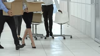 Multi-ethnic team of office workers walking through hallway towards the camera while moving into new office, chatting and carrying belongings