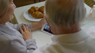 Over the shoulder PAN of retired elderly people video calling family with grandchild while relaxing in cafe