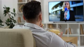 Over the shoulder shot of man eating chips from glass bowl and watching news on TV while sitting on sofa in the living room