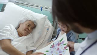Over the shoulder shot of unrecognizable male doctor holding drawing of little girl talking and hugging her sick grandmother lying in hospital bed