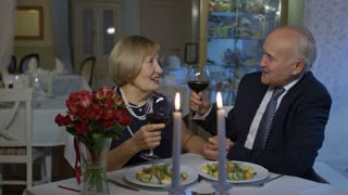 PAN of affectionate senior man in suit and happy elderly woman clinking glasses and drinking expensive wine on romantic date in restaurant