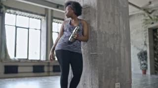 PAN of African woman holding sports water bottle and leaning on wall in empty fitness studio, then looking at camera and smiling