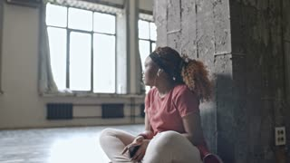 PAN of African woman sitting in empty dance studio and listening to music in earphones, then looking at camera and smiling