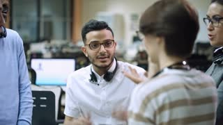 PAN of Arab call centre operator with headset changing glasses with female colleague while coworkers chatting on break