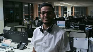 PAN of Arab male call centre worker in glasses posing in camera in empty office
