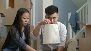 PAN of Asian couple sitting on floor of their new apartment and checking their new lamp