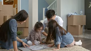 PAN of Asian family with little children sitting on floor on empty living room of new house and looking through folder with furniture layout ideas