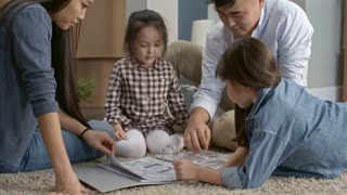 PAN of Asian family with little girls sitting on floor on living room of their new flat and looking through folder with furniture layout ideas