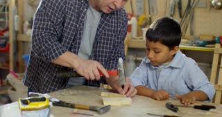 PAN of Asian father teaching little boy how to drive nails into wood: he is giving hammer to curious son and watching him try