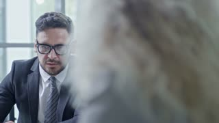 PAN of businessman in suit and glasses and his male colleague with grey hair looking at laptop and discussing project with unrecognizable businesswoman during meeting in conference room