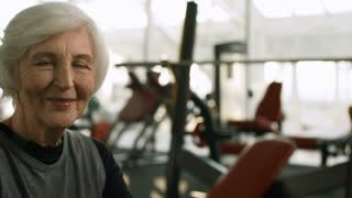 PAN of cheerful senior woman with grey hair looking at camera and smiling in gym