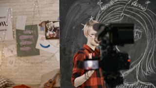 PAN of cheerful teenage blogger in glasses and plaid shirt standing before blackboard with drawing and talking while filming herself on video camera standing on tripod