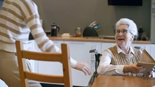 PAN of cheerful young female social worker with household bills sitting down at kitchen table and talking to smiling elderly lady in wheelchair
