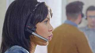 PAN of concentrated female call centre operator in headset with microphone talking with customer on voice call in office; male and female colleagues talking in background