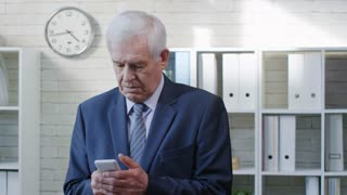 PAN of concentrated senior businessman in suit typing on mobile phone in office