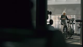 PAN of determined elderly lady in fitness clothes training on cycling machine in gym