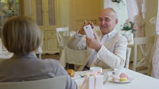 PAN of elderly man holding mobile phone and taking photo of his senior wife on date in cozy restaurant