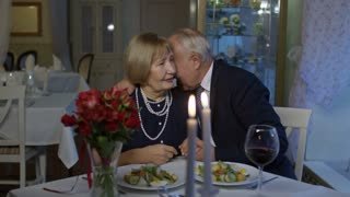 PAN of elderly man hugging his senior wife and saying toast, then drinking wine during romantic date in restaurant