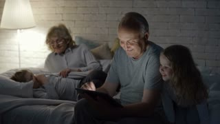 PAN of elderly man with tablet showing something to adorable girl with blond hair while senior lady in glasses lying on bed with laughing little boy and chatting