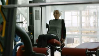 PAN of elderly woman in fitness clothes doing exercise on leg curl machine in gym