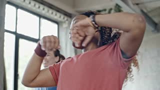 PAN of energetic African woman with curly hair dancing zumba in group class