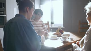 PAN of family eating breakfast in morning: cheerful woman cutting pie and giving pieces to senior lady and young man with ponytail