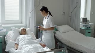 PAN of female Asian doctor in lab coat holding clipboard with chatting with elderly patient lying in hospital bed