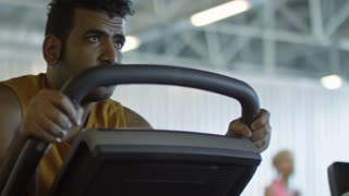 PAN of focused Arab man and black woman training on stationary bikes in gym