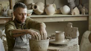 PAN of focused bearded male artisan in apron wetting his hands and throwing vase on spinning pottery wheel in workshop