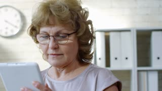 PAN of focused mature businesswoman standing in office and typing on tablet