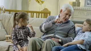 PAN of grandfather with grey hair sitting on sofa and telling story to grandchildren