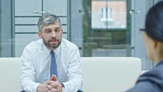 PAN of grey haired businessman with beard wearing shirt and tie sitting on sofa in airy office with glass walls and discussing work with businesswoman; people riding transparent elevator in background