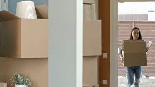 PAN of happy Asian couple carrying rolled up carpet and cardboard box, then putting them down on floor of their new house