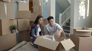 PAN of happy Asian couple sitting on floor of their new house and unpacking cardboard box with lamp