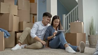 PAN of happy Asian couple sitting on floor on their new house and looking at tablet