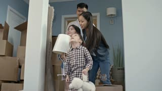 PAN of happy Asian family with children looking around their new house after moving
