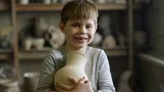 PAN of happy cute little boy holding ceramic vase and smiling for camera in pottery workshop