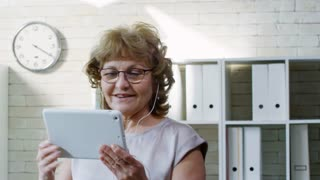 PAN of happy elderly businesswoman in glasses holding tablet and chatting with someone on video call in office: she waving hello and smiling