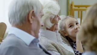 PAN of happy grandmother laughing and chatting with cute elementary age girl sitting on her laps, then talking with unrecognizable grandson