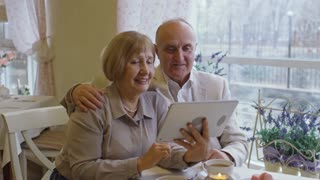 PAN of happy grandparents sitting in cafe and talking with family on video call via tablet