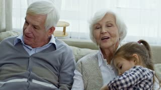 PAN of happy grandparents with grey hair laughing and spending time with their grandchildren