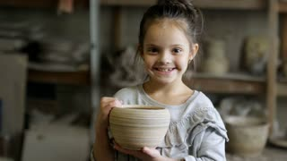 PAN of happy little girl holding ceramic pot and smiling for camera in pottery workshop