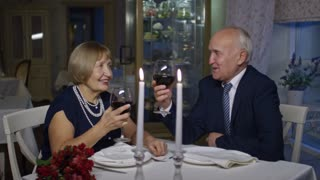 PAN of happy senior man and woman clinking glasses and drinking wine on romantic date in restaurant